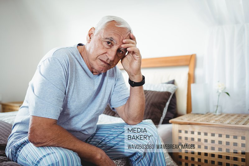 Portrait of frustrated senior man sitting on bed in bedroom