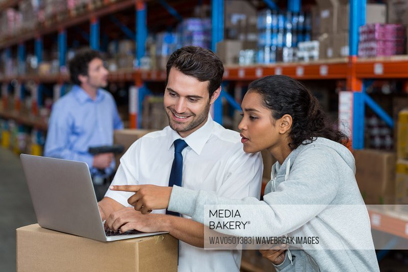 Warehouse worker working on laptop in warehouse