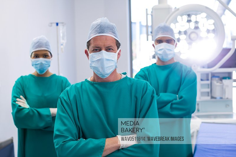 Team of surgeons wearing surgical mask in operation theater of hospital