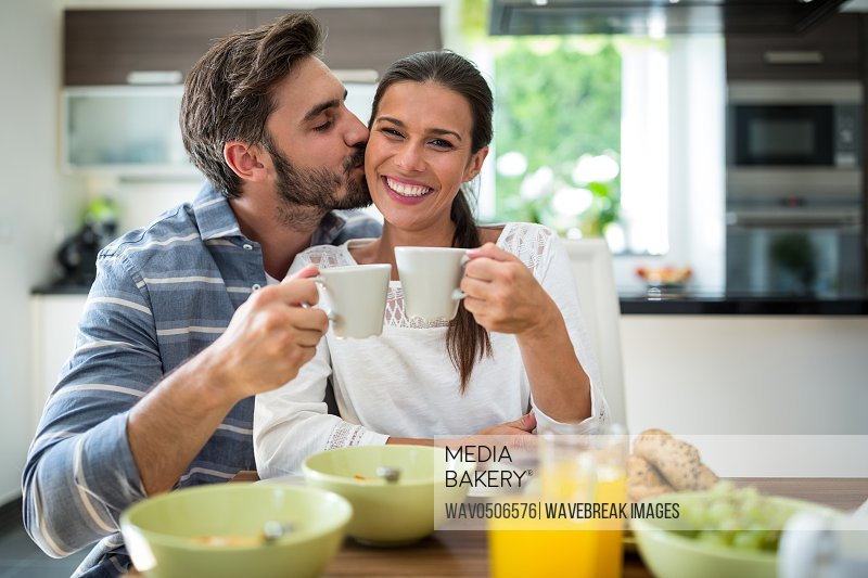 Man kissing on woman cheeks while having breakfast at home