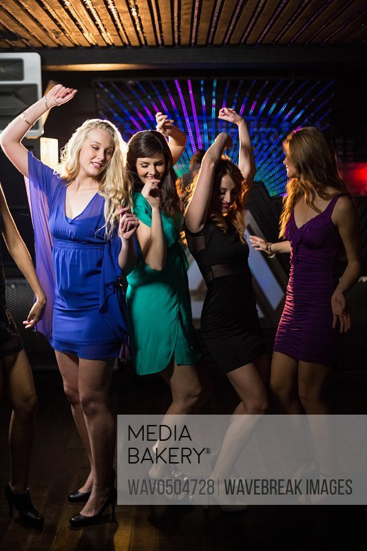 Group of smiling female friends dancing on dance floor in bar