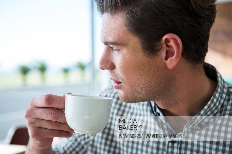 Thoughtful man looking out of the window while having coffee in coffee shop