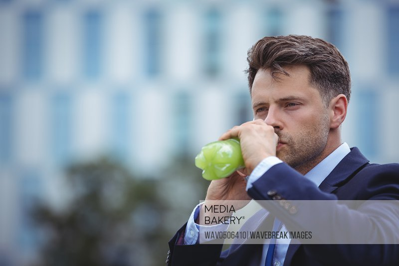Close-up of handsome businessman drinking juice
