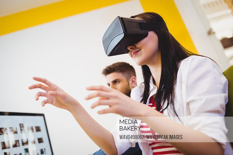 Low angle view of young female executive enjoying augmented reality headset at creative office