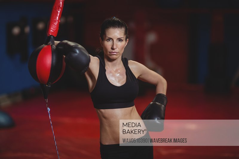 Female boxer leaning on speed boxing ball in fitness studio