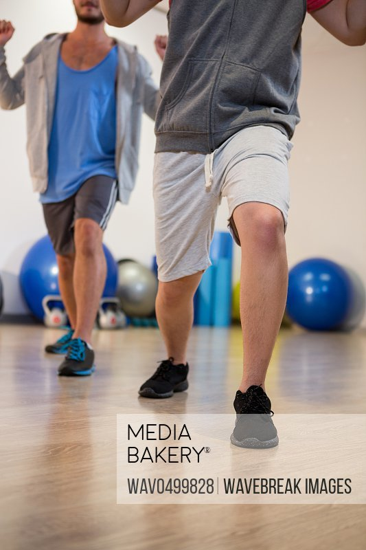 Men performing stretching exercise in gym