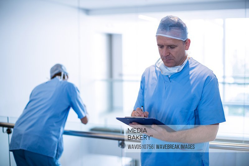 Male surgeon writing on a clipboard at hospital