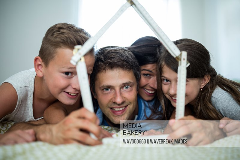 Happy family playing with model house in bedroom at home