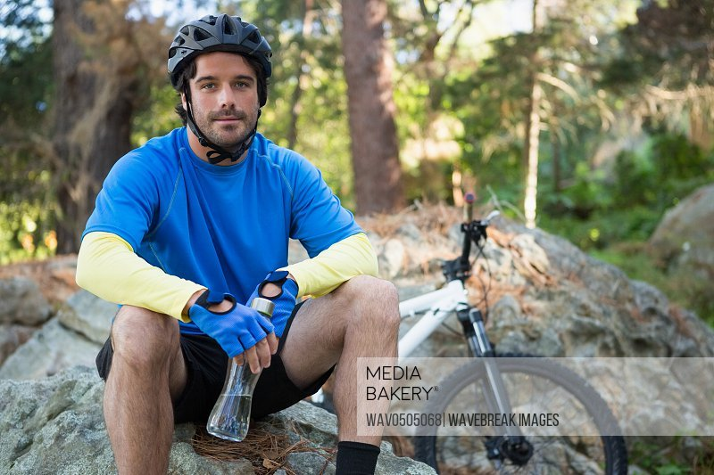 Portrait of male mountain holding water bottle and relaxing on a rock in the forest