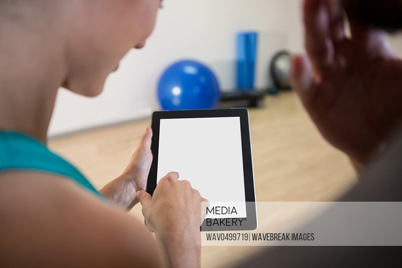 Woman showing digital tablet to trainer in fitness studio