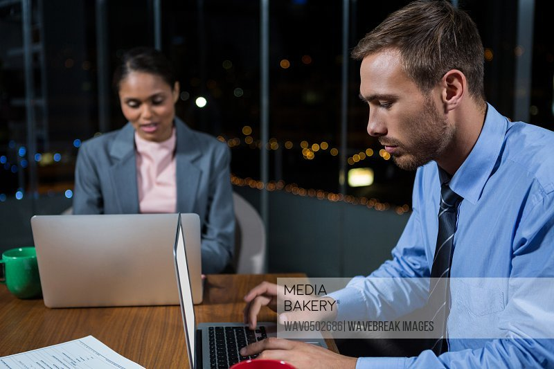 Businessman and businesswoman working in office at night