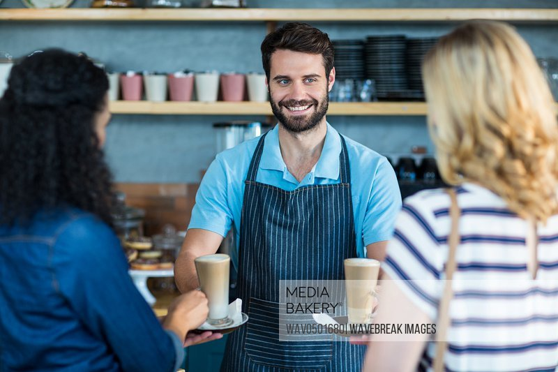 Waiter serving a cup of coffee to customer at counter in cafA?