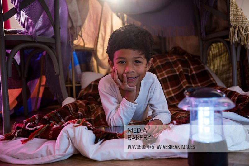 Portrait of boy with digital tablet relaxing on mattress at home