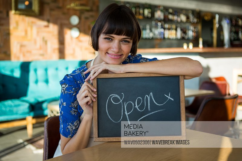 Portrait of smiling woman sitting in the coffee shop with a open sign