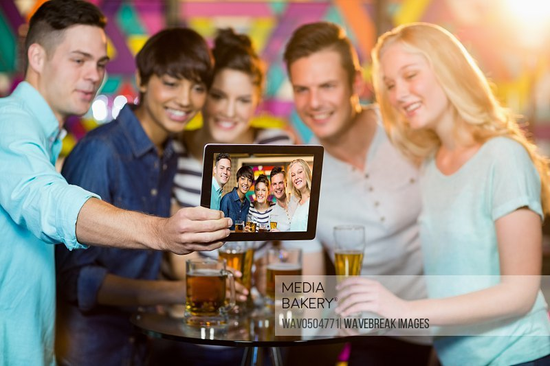 Group of smiling friends clicking a photo from digital tablet in bar