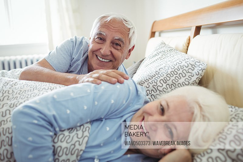 Portrait of happy senior couple lying on bed in bedroom