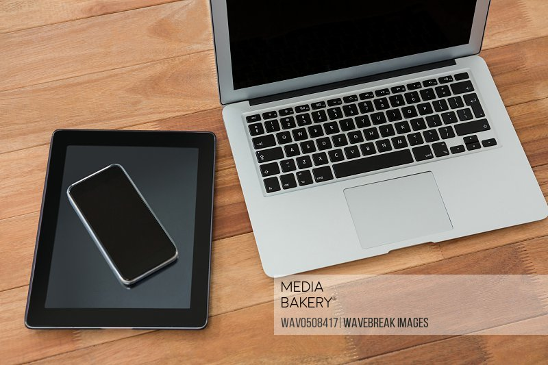 Close-up of laptop digital tablet and mobile phone on table against white background