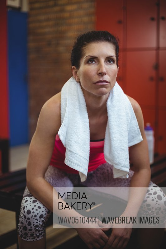 Thoughtful woman sitting in locker room after workout