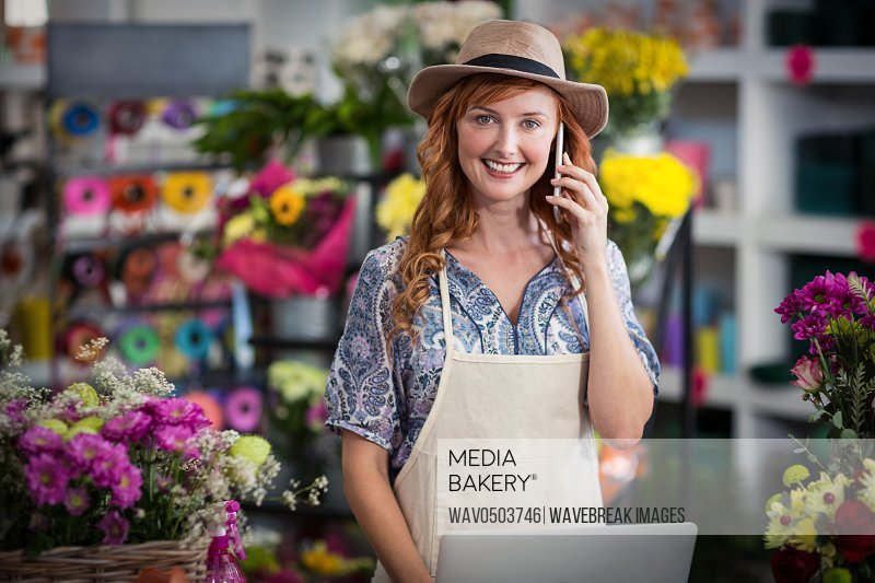 Portrait of female florist talking on mobile phone while using laptop in flower shop