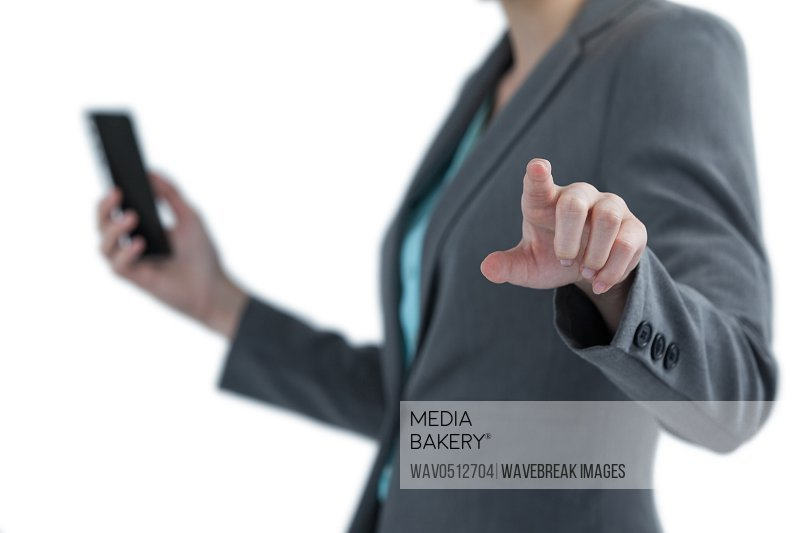 Mid section of businesswoman holding mobile phone and using digital screen against white background