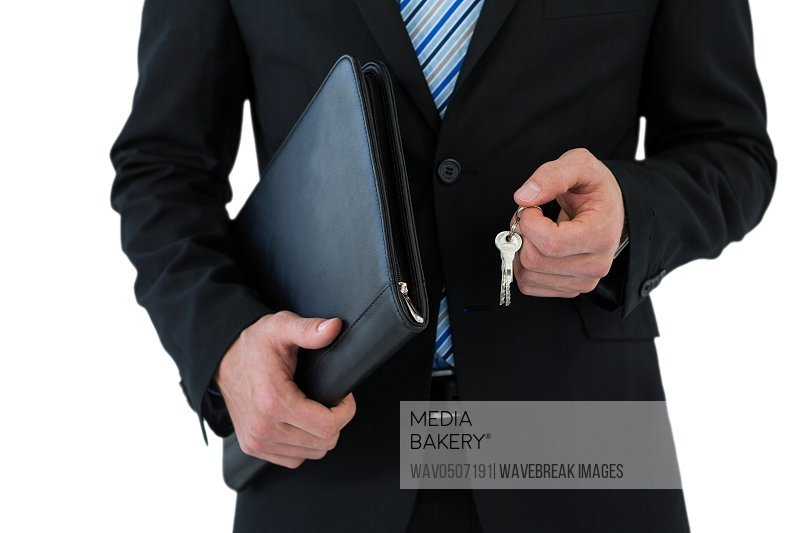 Mid section of businessman holding keys on white background