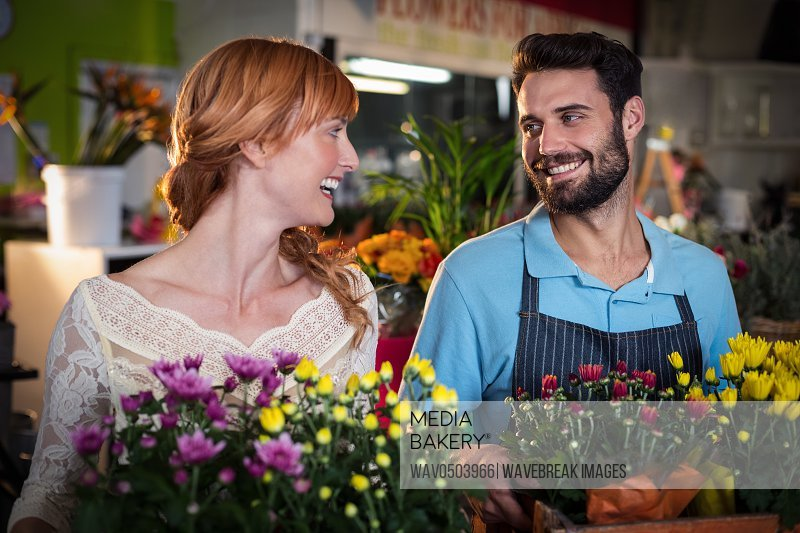 Couple holding crate of flower bouquet in the flower shop