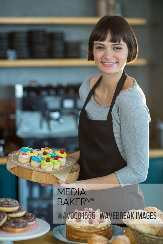Portrait of smiling waitress holding cup cake on tray in cafA?
