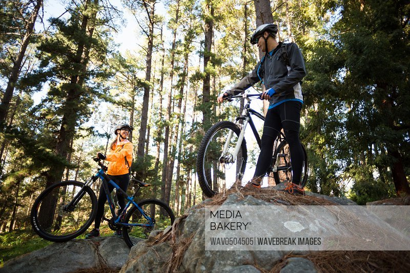 Biker couple standing with their mountain bike in forest at countryside