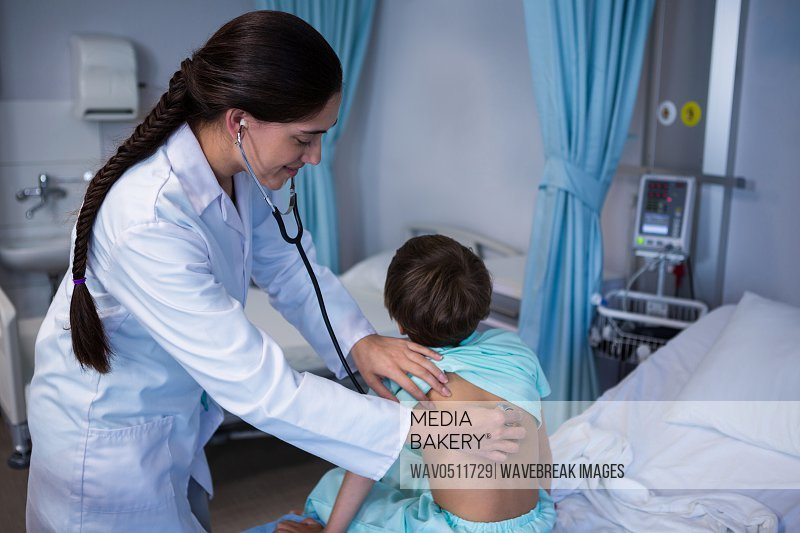 Female doctor examining patient with stethoscope in ward at hospital