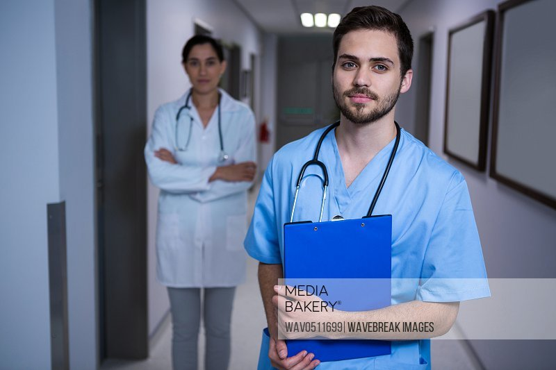 Portrait of male nurse standing with doctor in background at hospital corridor