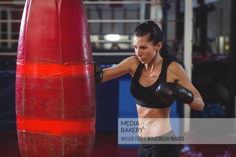 Female boxer practicing boxing with punching bag in fitness studio