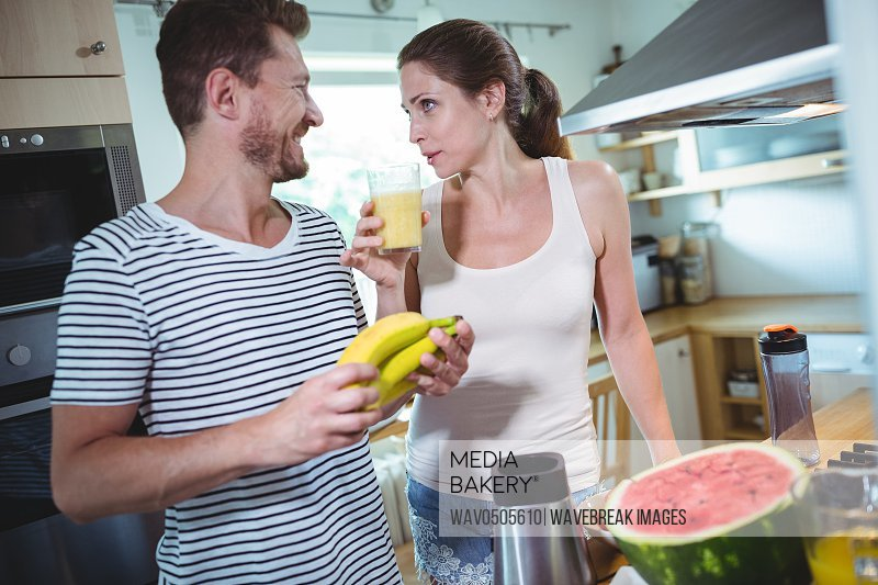 Couple holding banana and drinking smoothie in kitchen at home