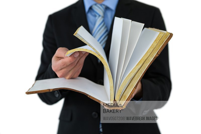 Mid section of businessman flips through the pages of a book on white background