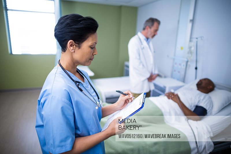 Female nurse writing on clipboard during visit in ward of hospital