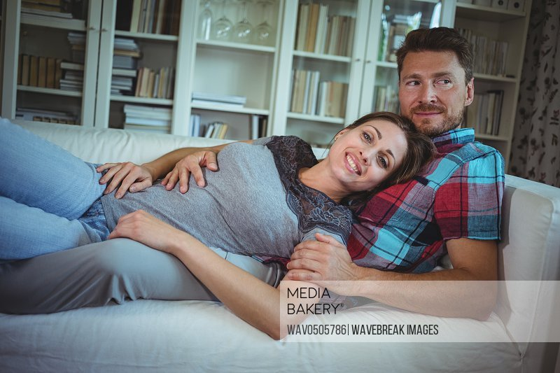 Happy couple lying on sofa in living room at home