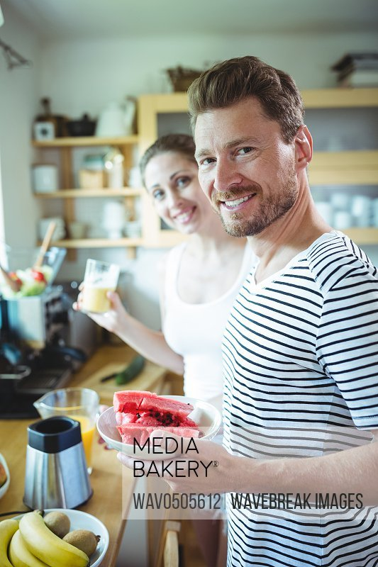 Smiling couple holding plate of water melon in kitchen at home