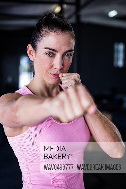 Portrait of confident female athlete punching in gym