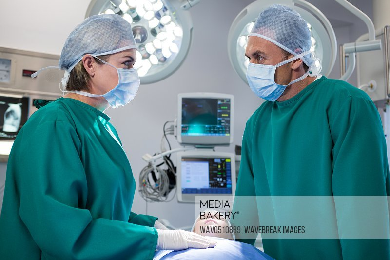 Surgeons interacting while operating patient in operation theater