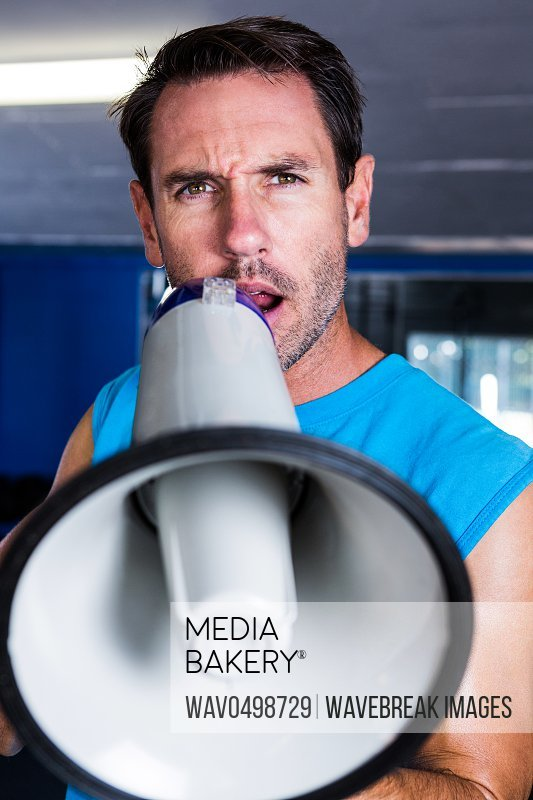 Portrait of fitness instructor using megaphone in gym