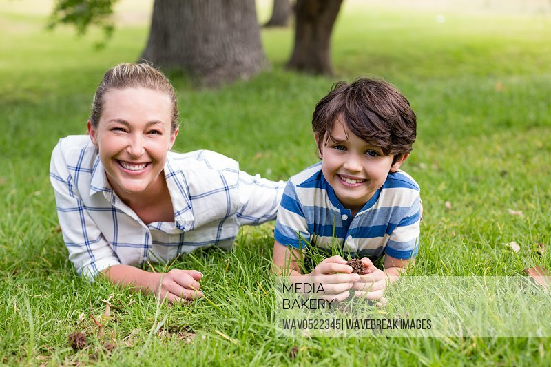 Portrait of mother and son lying in park on a sunny day