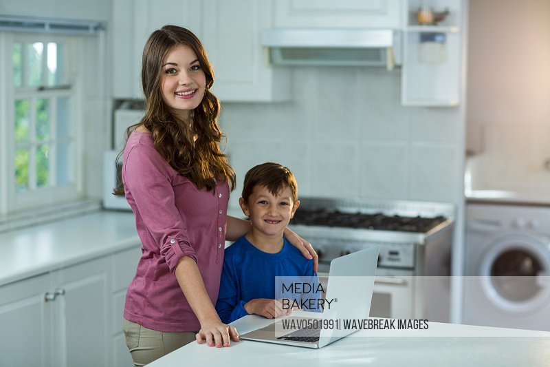 Mother and son with laptop at kitchen