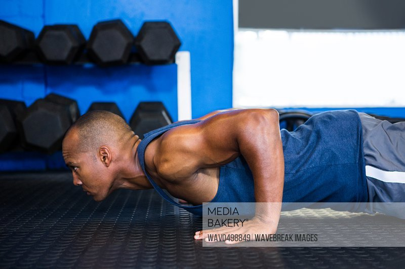 Side view of male athlete doing push-ups in gym