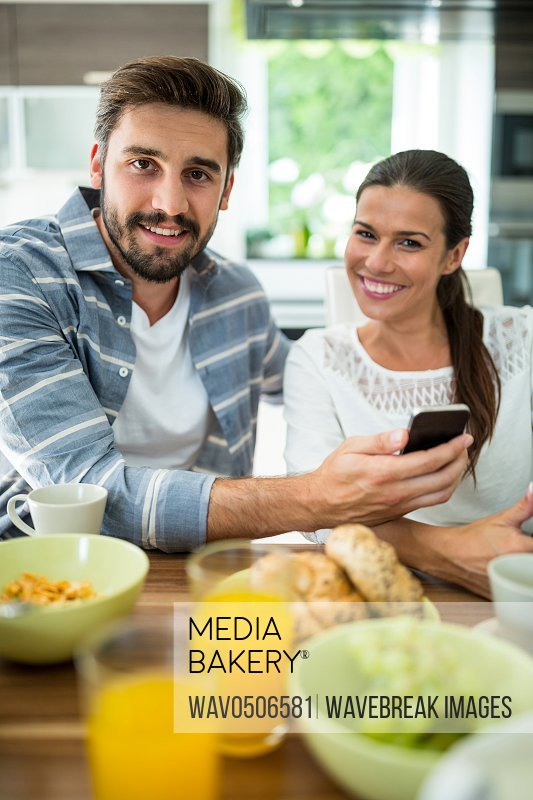 Portrait of couple using mobile phone while having breakfast at home