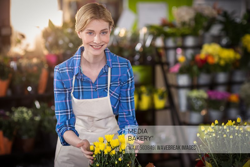 Female florist touching flower bouquet in the shop
