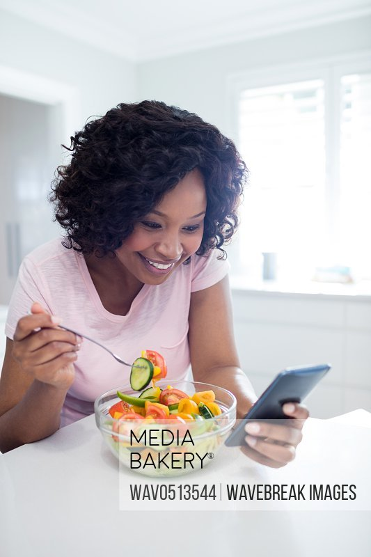 Woman having salad while using mobile phone