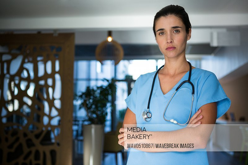 Portrait of female surgeon standing with arms crossed in hospital
