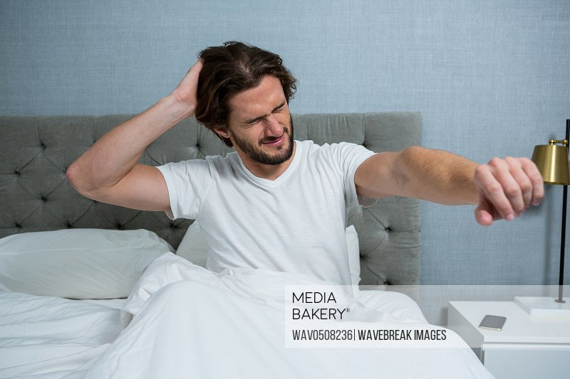 Man waking up in bed and stretching her arms in bedroom