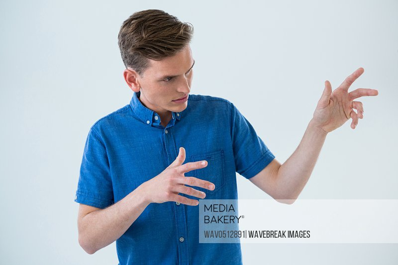 Man in blue shirt making hand gesture against white background