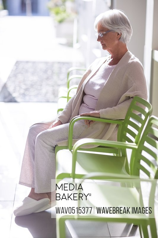 Thoughtful senior woman sitting on chair