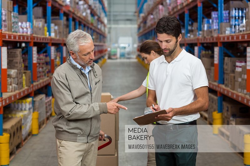 Warehouse manager and male worker interacting while working in warehouse
